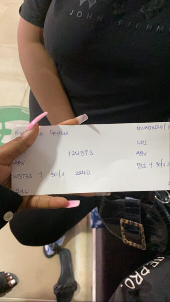 Nigerian lady shows off the boarding pass she got at an airport